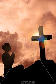 stock photo of praying silhouetted against sunset with