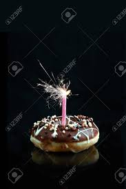 candle sparklers creative image of a chocolate smothered donut with pink candle