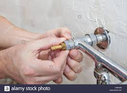 two handle kitchen faucet repair close up plumber hands