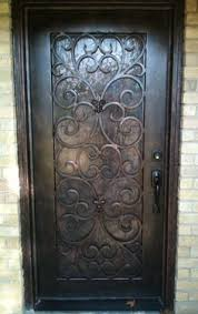 a custom arched door with an artsy scroll wrought iron grate