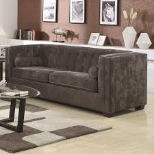 what is transitional style solemn grey velvet tuxedo couch with oval top glass cocktail table