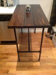hand made reclaimed wood and black iron pipe table by reformed