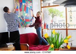 Young Couple Room Young Couple Putting Up Painting In Living Room Stock Photo
