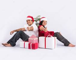 young indian couple sitting with with christmas gifts showing card