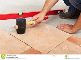 installing ceramic flooring fitting a tile royalty free stock