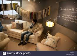 man trying out couches in store london uk stock photo royalty