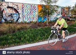 gainesville florida sw depot avenue wall mural art asian girl gainesville florida sw depot avenue wall mural art senior woman riding bicycle bike stock photo