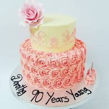 two tier pink and cream cake with roses and stencil the on