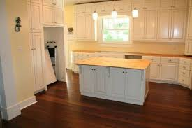 white kitchen with bamboo kitchen flooring and silver appliances