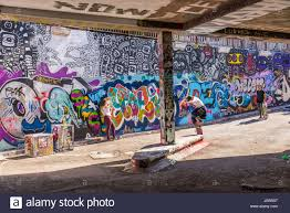 teenager skater riding a skateboard performing an trick in leake stock photo teenager skater riding a skateboard performing an trick in leake street tunnel london uk leake street also known as