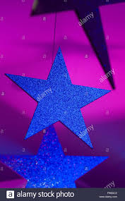 large stars covered in glitter hang from ceiling an event