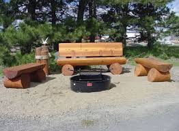log bench around a campfire pit in the back yard for the home