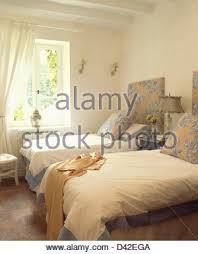 white duvets on twin beds in white spanish country bedroom stock