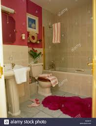 fluffy red bathmat on floor of red bathroom with cream tiles stock