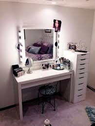 stylish small makeup vanity desk with lighted mirror beside tall graded cabinet drawers featuring french wrought iron chair