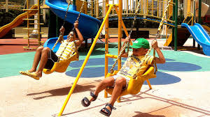 children in the park with slide swing rock wall