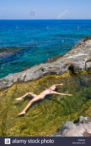 woman floating in colorful water pool by the sea pantelleria