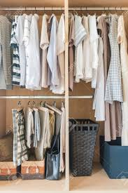 clothes and dress hanging on rail in wooden closet at home stock