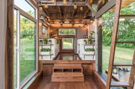 out tiny home features garage door and custom deck curbed