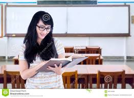 student standing in class while reading book stock photo image
