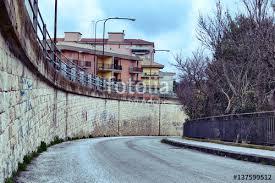 ringhiera metallica strada urbana con ringhiera metallica a destra e muro in pietra a