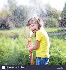 cheerful kid watering plants from hose spray in garden at backyard