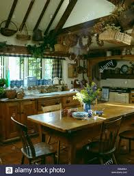 old wooden table and chairs in country kitchen with baskets and