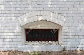 small arched basement window with bars in a white brick wall stock
