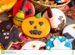 different halloween cookies on table with autumnal leaves stock