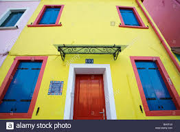 burano italy yellow house with blue shutters and red wooden door