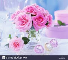 pink roses in glass chocolates and gift boxes beside it stock