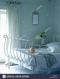 white wrought iron bed with pale blue quilt in cottage bedroom