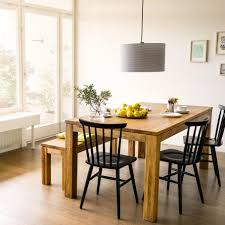 rustic wood dining table with bench and black metal chairs of
