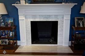 white fireplace surround with shelf above and white marble frame