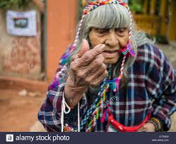 an elderly indigenous woman with very wrinkled skin in native