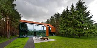 unusual glass modern house in forest design with elegant terrace