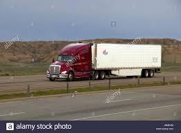 kenworth semi a red or maroon kenworth semi truck pulls a white trailer along a