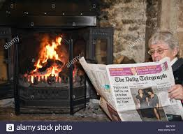 senior woman pensioner reading a daily telegraph broadsheet
