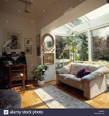 comfy sofa in front of window in small glass extension of