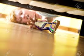 woman looking for her shoe under the bed stock photo picture and