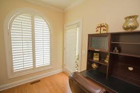 wood shutters transform arched windows into the ultimate style