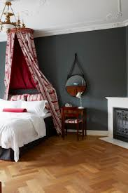 bedroom with parquet flooring and wall painted in down pipe from