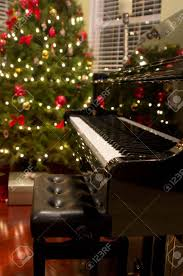 baby grand piano with christmas tree presents in background