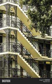 external stairs with decorative black iron lace railings on a