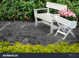 Chair In Garden White Wood Chair And Flower Pot With Pink Flower On Floor In