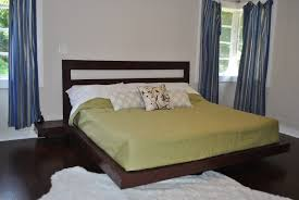 brown teak bed frame with mocha blanket and black wooden headboard