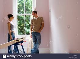 couple doing diy at home standing beside window woman holding glue