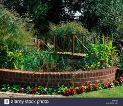 raised garden pond with brick surround and bridge stock photo