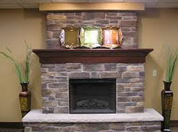 stacked stones fireplace ideas displaying with classic fireplace surroundantel with two big glass vases and some iron accessories