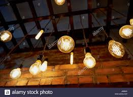 edison light bulb hanging on a long wire cozy warm yellow stock